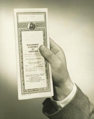 Businessman holding insurance policy, close-up of hand, (B&W)