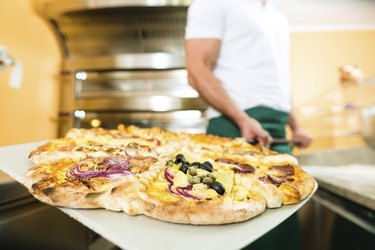Man pushing the finished pizza from oven