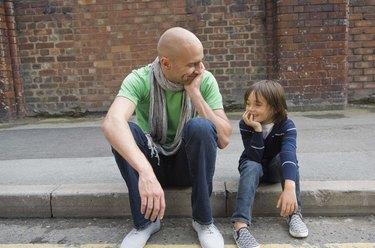 Father and son sitting on curb