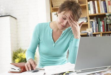Woman by laptop in home office, hand on forehead