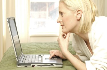 Woman using laptop computer in hotel room