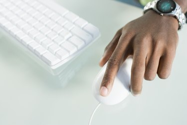 High angle view of a man's hand operating a computer mouse