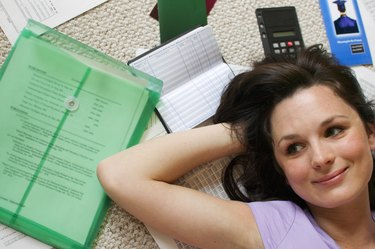 Woman lying on floor with paperwork