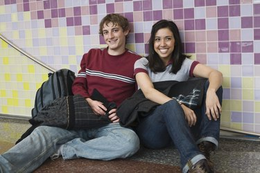 Multi-ethnic couple sitting against wall