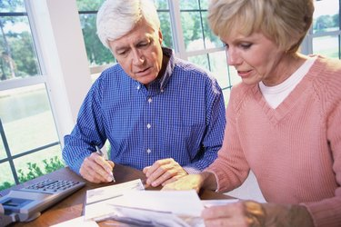 Senior couple sitting together calculating bills