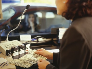 Teller counting money in drive threw bank window