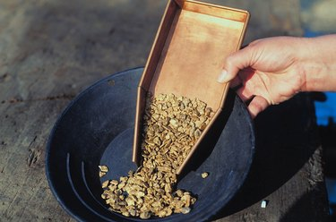 Person pouring gold nuggets into a pan