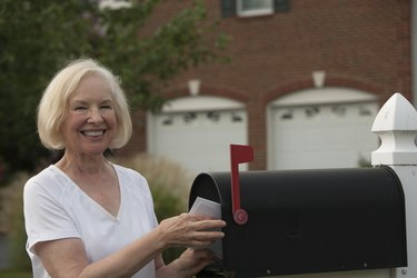Smiling senior woman putting mail from her mailbox