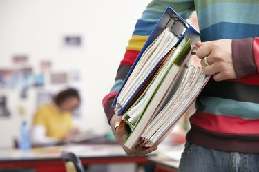 Young Man Carrying File Folders