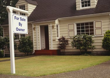 For Sale sign on front lawn of house