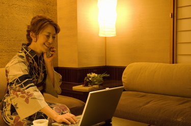 Woman talking on a mobile phone and using a laptop