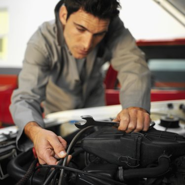Close up of an car engine being repaired by a male mechanic holding a spanner