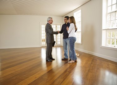 Couple shaking hands with realtor in empty room