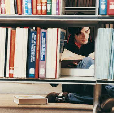 Male University Student Reading in a Library Behind Shelves
