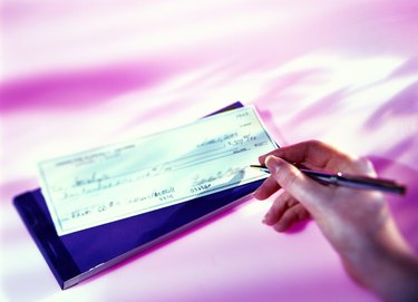 high angle view of a woman's hand writing a cheque