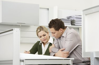 Businessman and businesswoman working at desk in office