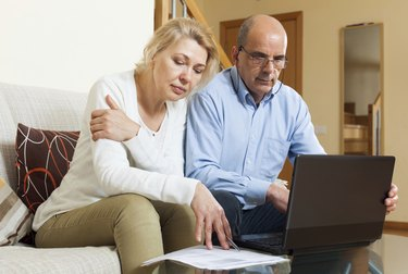 Family reading finance documents together and using laptop