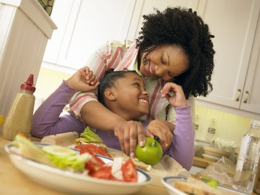 Mother Stands With Her Young Daughter in the Kitchen, Chopping an Apple for Her Lunch