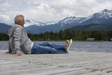 Senior man sitting on pier, looking at view, mountain range in background
