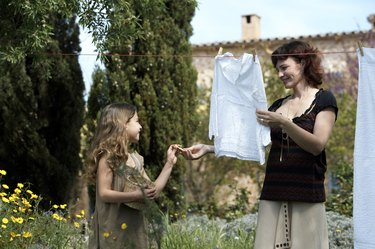 Mother and daughter (8-9) hanging laundry in garden