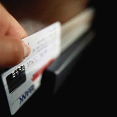 Person swiping credit card, close-up (focus on hand)