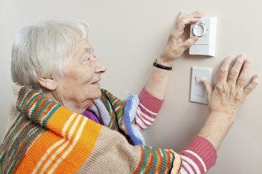 Senior woman adjusting her thermostat
