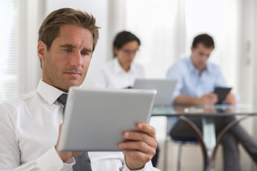 Businessman using his digital tablet in the office