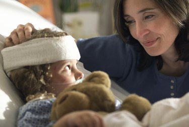 a caucasain mother visits and consoles her young child as she lays recovering in the hospital