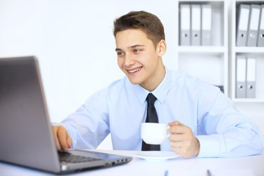 Young smiling businessman with cup of coffee in office