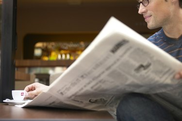 """Man sitting at cafe table reading newspaper, reaching for cup"""