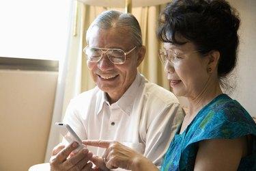 Senior couple holding mobile phone, smiling