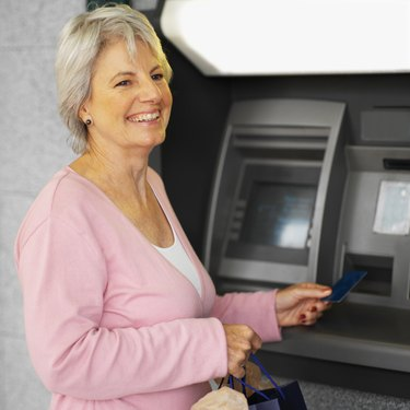 Close-up of senior woman inserting bank card into atm machine