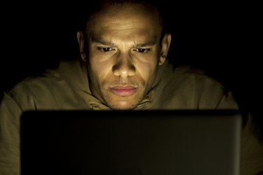 Concentrating man on his laptop at night