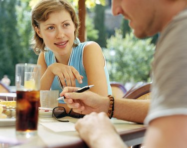 Couple having drink at outdoor cafe (focus on woman)