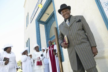 Well Dressed Man Outside a Church Standing and Looking at the Camera, with the Priest and Members of the Congregation in the Background