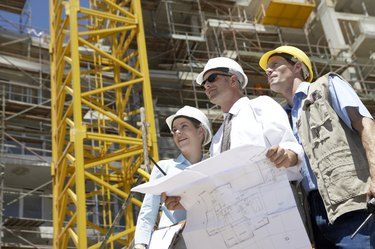 Three People Wearing Hard Hats on a Building Site, with One Man Wearing Sunglasses and Holding Blueprints