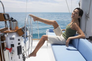 Asian woman steering sailboat with feet