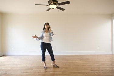 Woman on cell phone in empty room of new home
