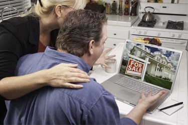 Couple In Kitchen Using Laptop - Real Estate