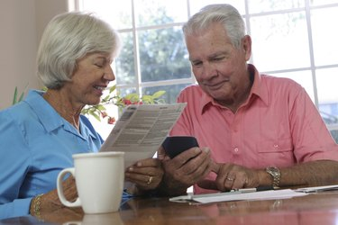 Close-up of a senior couple looking at a calculator