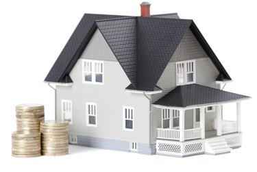 Coins in front of home architectural model