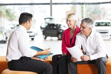 vehicle salesman explaining contract to senior couple