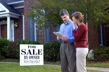 Couple reading real estate listings in front yard