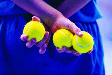 Person holding tennis balls behind back