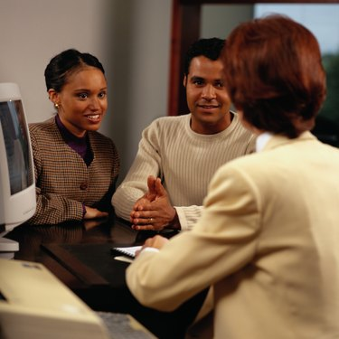 Couple with a Loan Officer Discussing a Home Loan