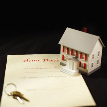Close-up of house deeds and keys with model house beside it