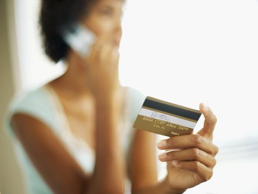close-up of a young woman talking on a mobile phone while holding a credit card