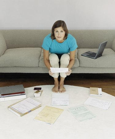 Elevated View of a Woman Sitting on a Sofa Surrounded by Bills