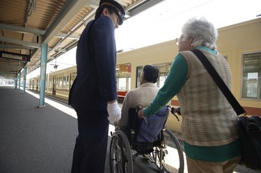 Conductor and senior couple at platform, senior man in wheelchair