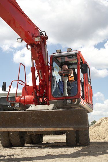 Construction worker sitting in cab of machinery